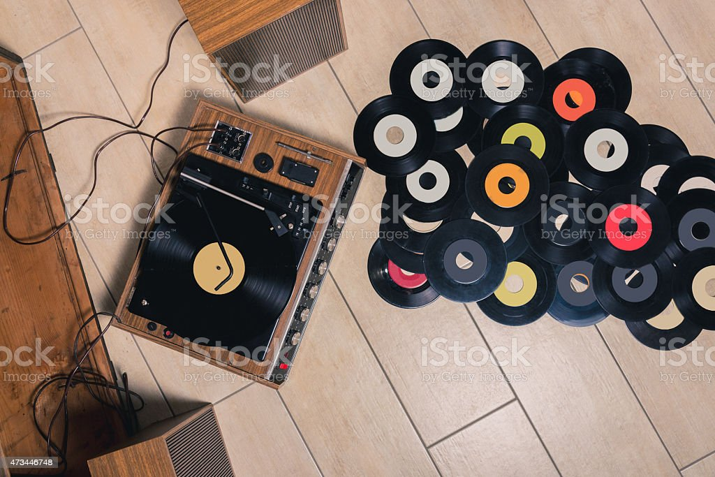 70's Turntable playing record with multiple vinyl on floor  stock photo