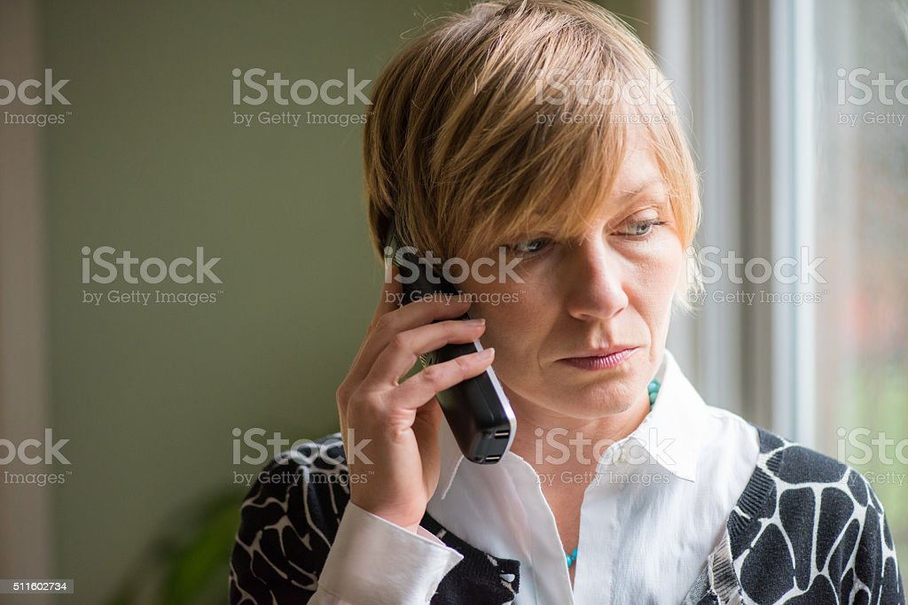 30's woman on a serious phone call. stock photo