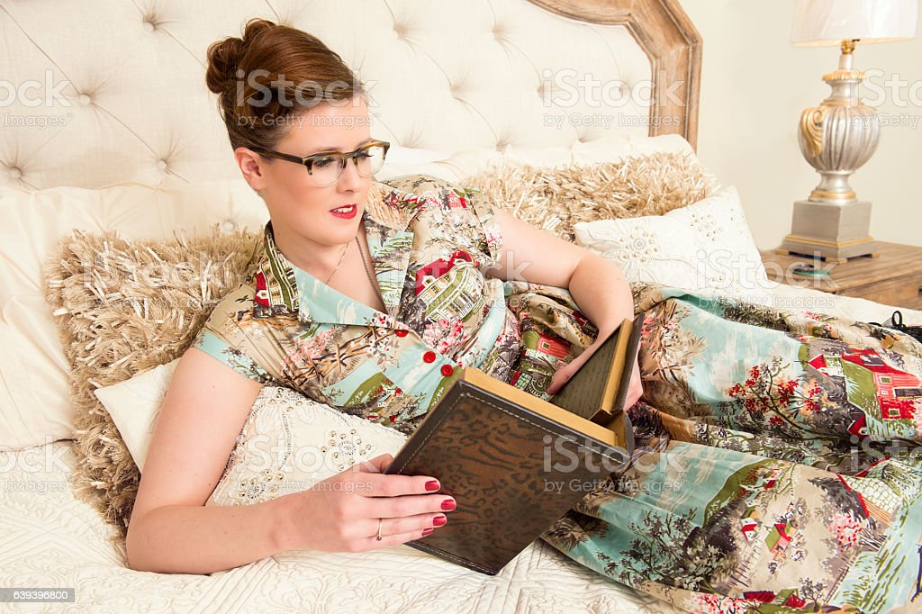 40's Woman Reading In Bed stock photo