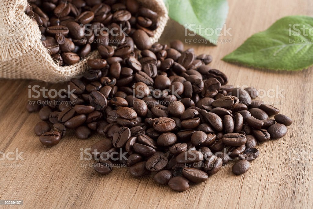A sac full of coffee beans that has spilled over  stock photo