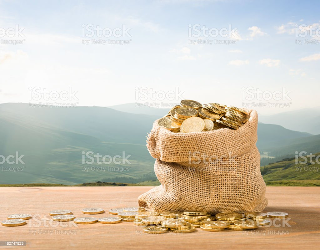 sack full of gold euro coins in outdoor setting stock photo