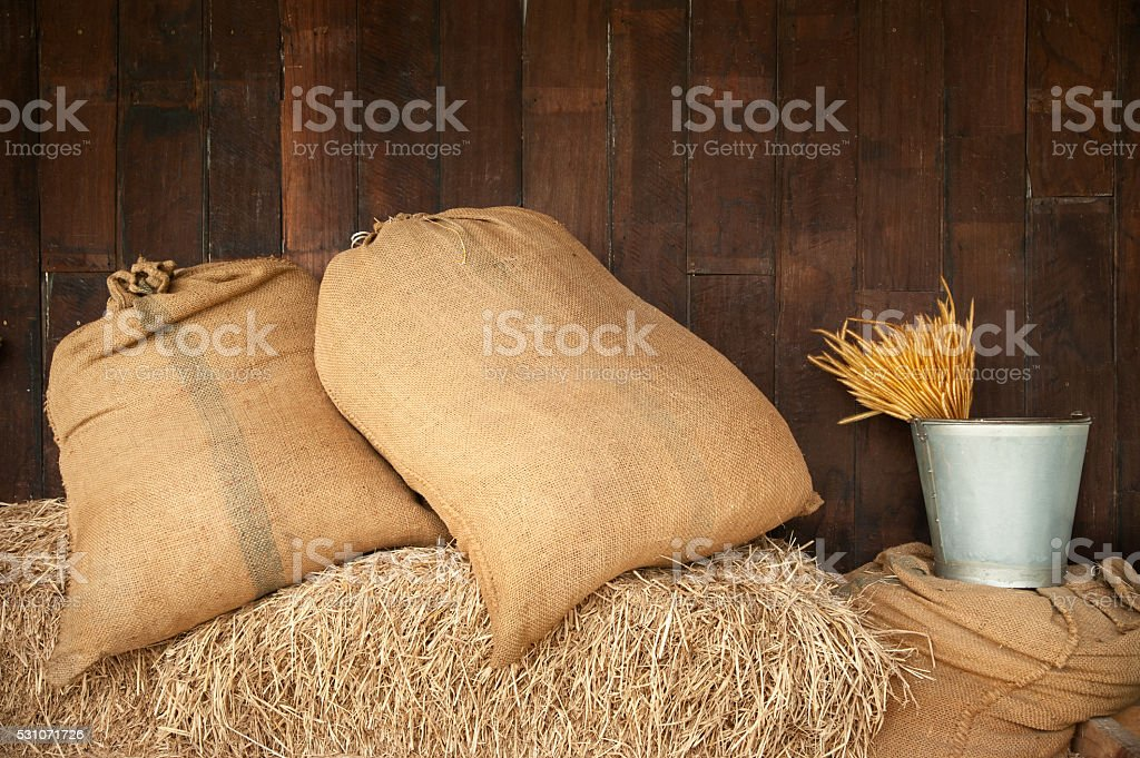 sack put one the stack of rice straw stock photo