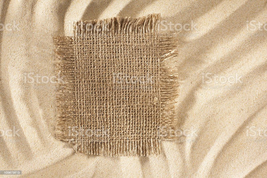 Sacking Patch with lacerate edge on waved sandy background stock photo