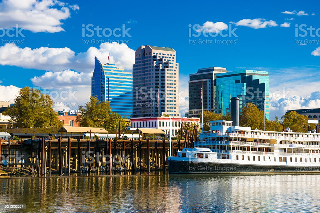 Sacramento skyline with blue sky, clouds, riverboat, and Sacramento River stock photo