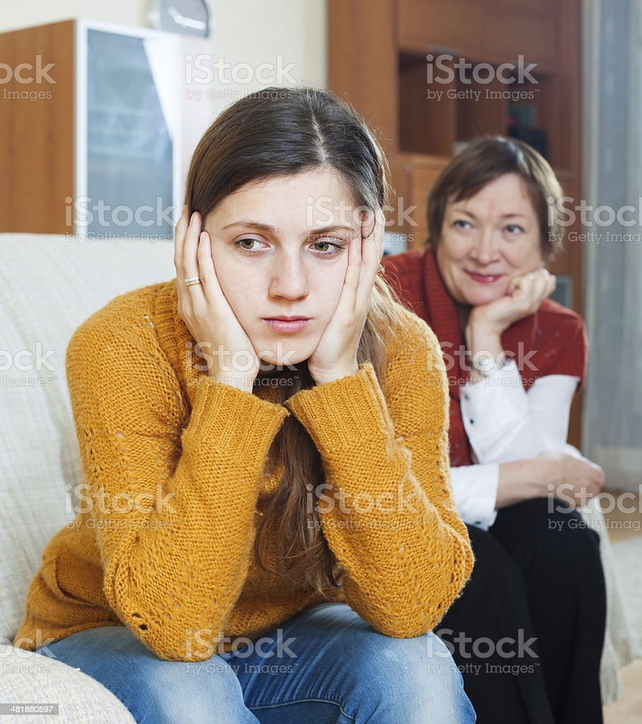 Sad adult daughter and mature mother after conflict stock photo