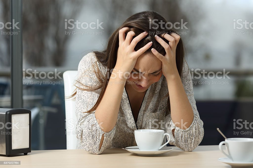 Sad and depressed woman alone in a coffee shop stock photo