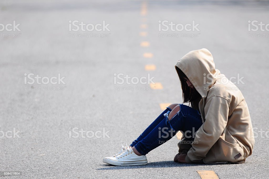 Sad and Heartbroken Girl Sitting on the Road stock photo
