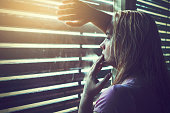Sad and lonely blonde woman looking through window blinds