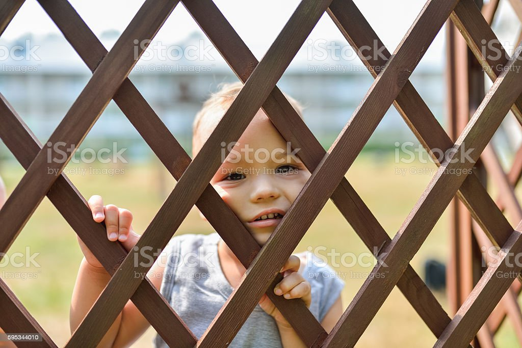 Sad and lonely child looking out through fence. Social problems stock photo