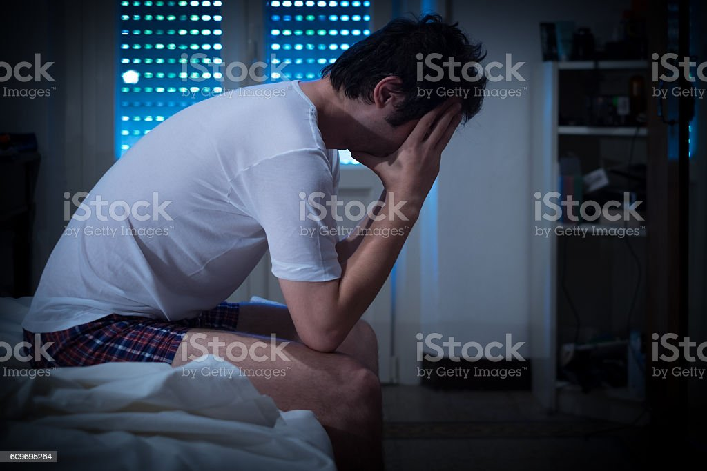 Sad and lonely man seated on his bed stock photo