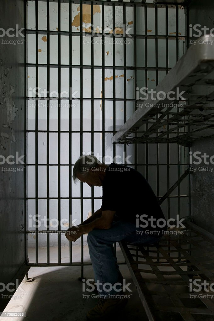 Sad and lonely older man in a prison cell stock photo