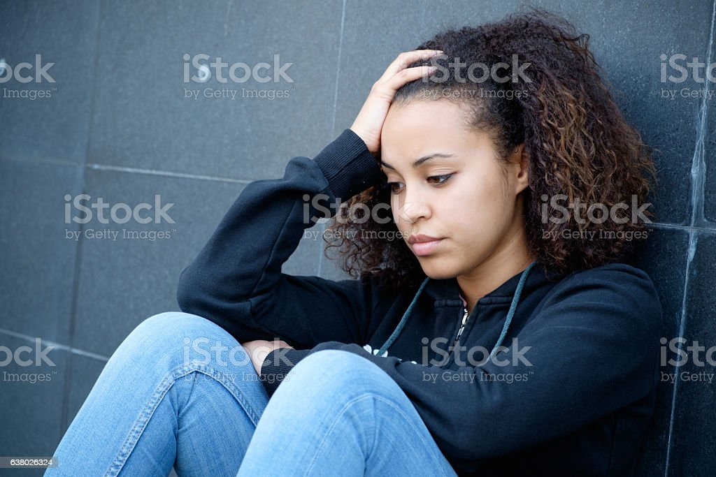 Sad and lonely teenager portrait in the city street stock photo