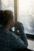 Sad and lonely woman looking out of the window