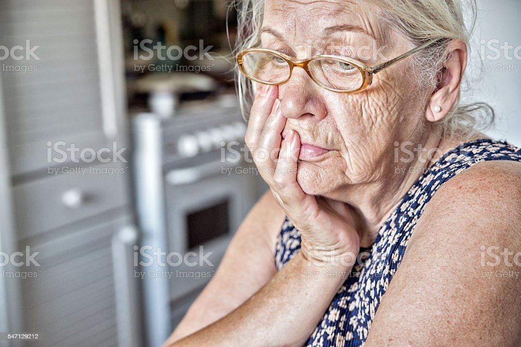 Sad and pensive Elderly woman in window light stock photo