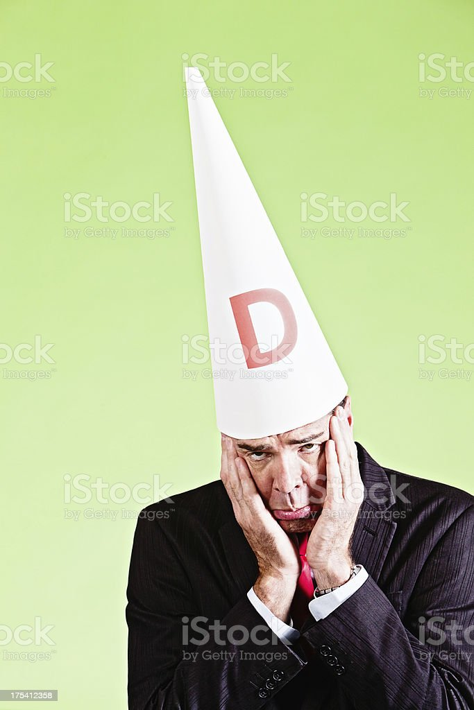 Sad ashamed businessman in dunce cap is sorry royalty-free stock photo