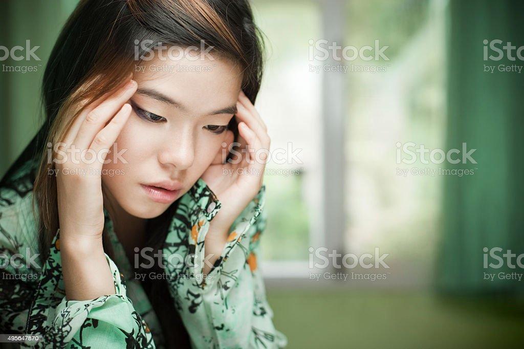 Sad Asian cute girl sitting near window holding her head. stock photo