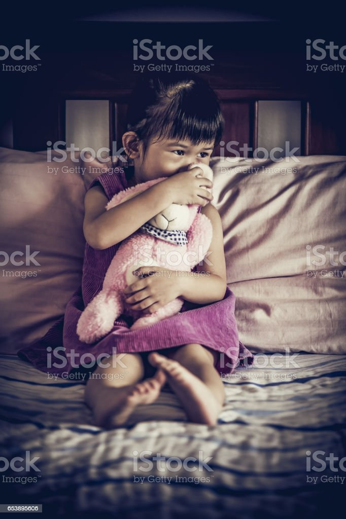 Sad asian girl sitting on bed. Vignette picture style. stock photo