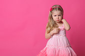 Sad baby in dress. Close up. Pink background