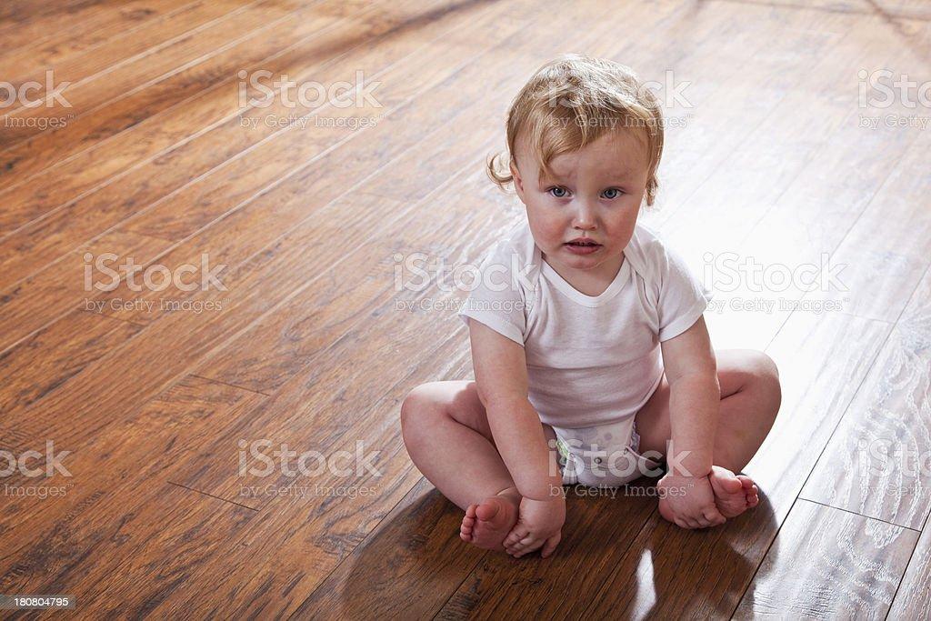 Sad baby sitting on floor royalty-free stock photo