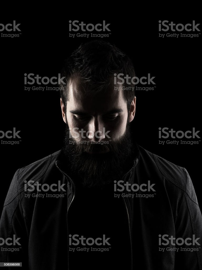 Sad bearded man looking down stock photo