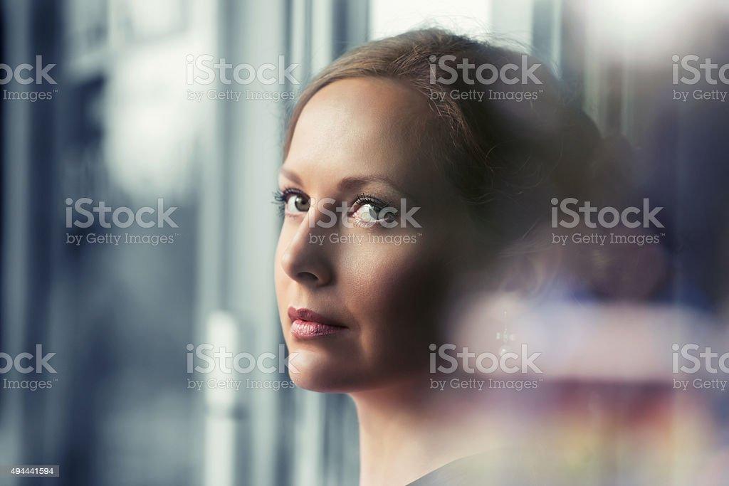 Sad beautiful woman looking out window stock photo