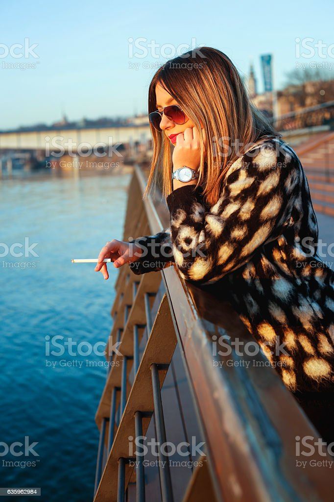 Sad beautiful woman standing on bridge and looking at river stock photo