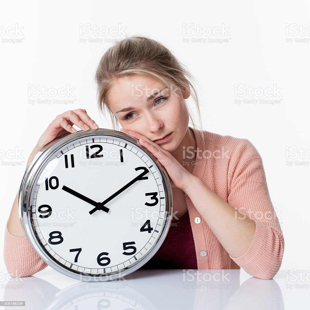 sad beautiful young blond woman leaning on a clock stock photo