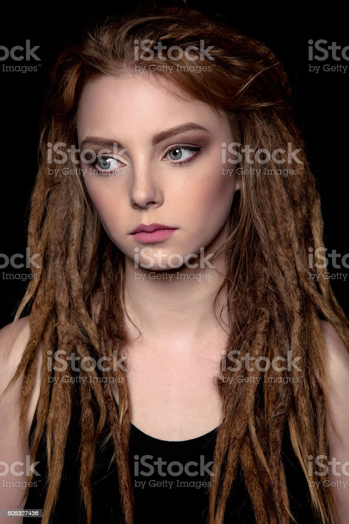 Sad Beautiful Young woman student with dreadlocks on black background