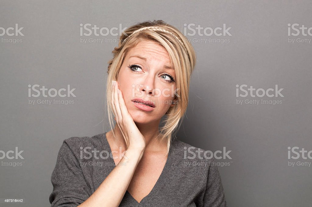 sad blond girl expressing fear and suspicion with her face stock photo