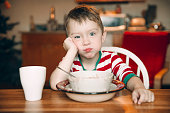 sad boy and a plate of porridge