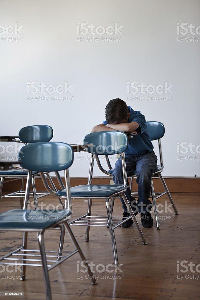Sad boy in a classroom stock photo