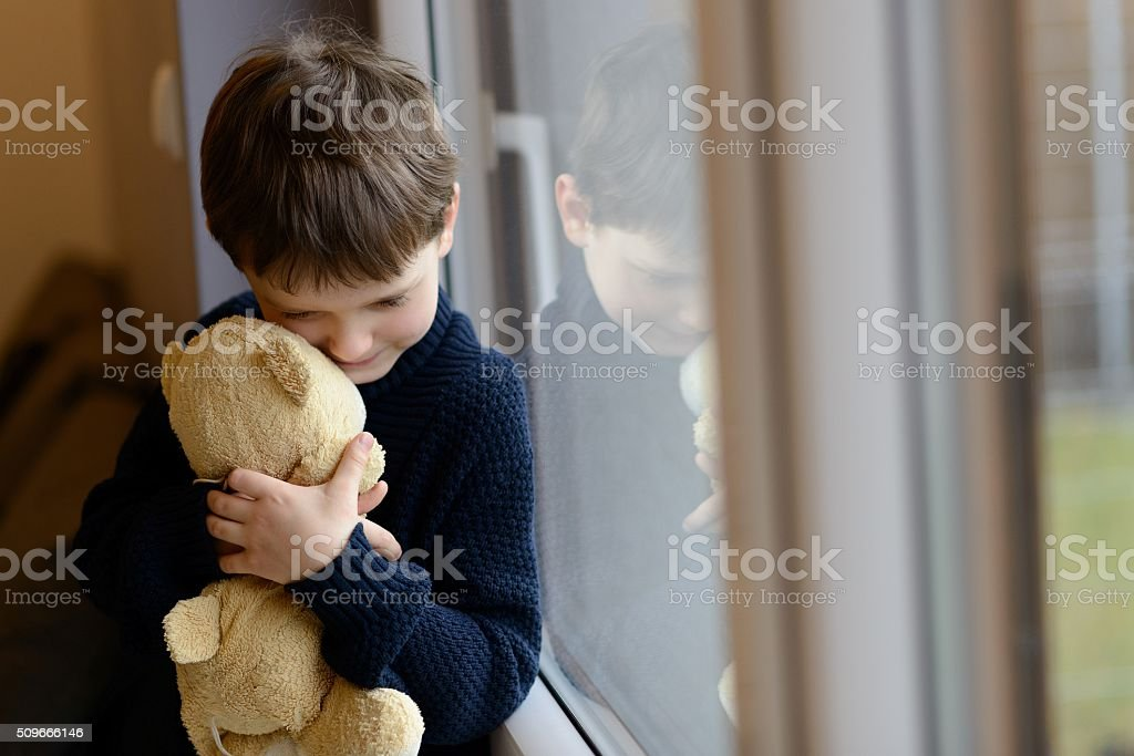 Sad boy is hugging his teddy bear. stock photo
