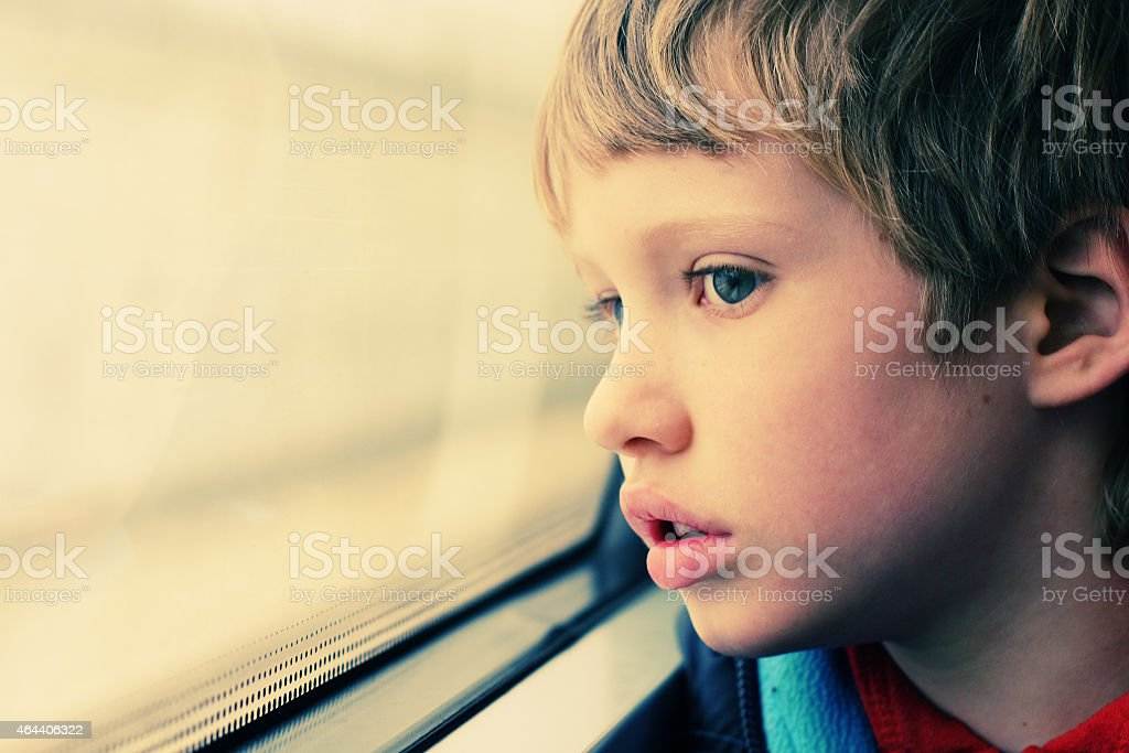 Sad boy looking out the window of a school bus stock photo