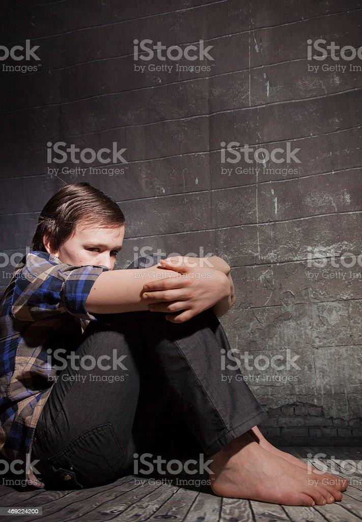 Sad boy sits about a wall. stock photo