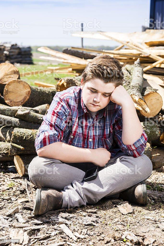 Sad boy sitting alone beside a farm woodpile royalty-free stock photo