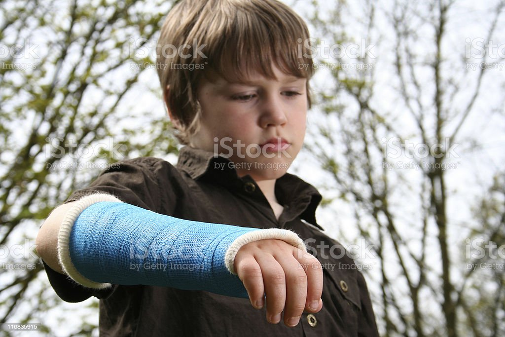Sad boy with broken arm in blue cast royalty-free stock photo