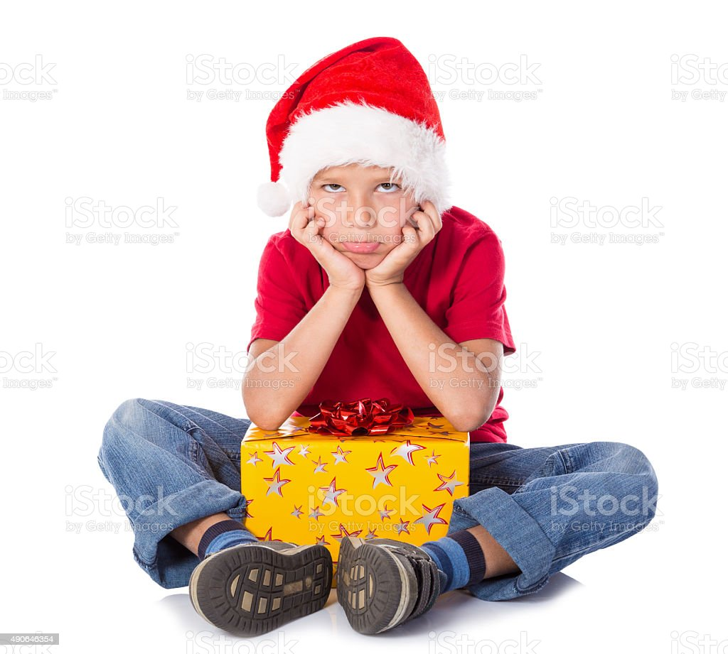 Sad boy with gift box in christmas hat stock photo