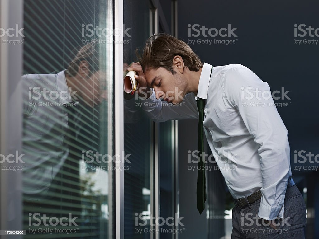 sad businessman leaning on window in office royalty-free stock photo