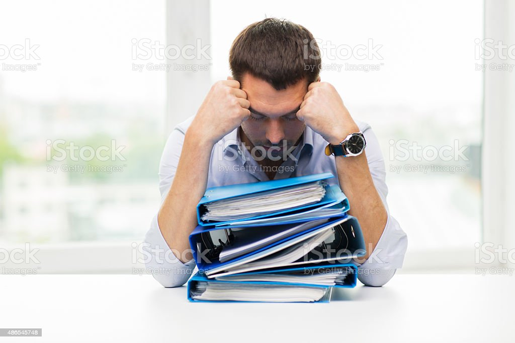 sad businessman with stack of folders at office stock photo