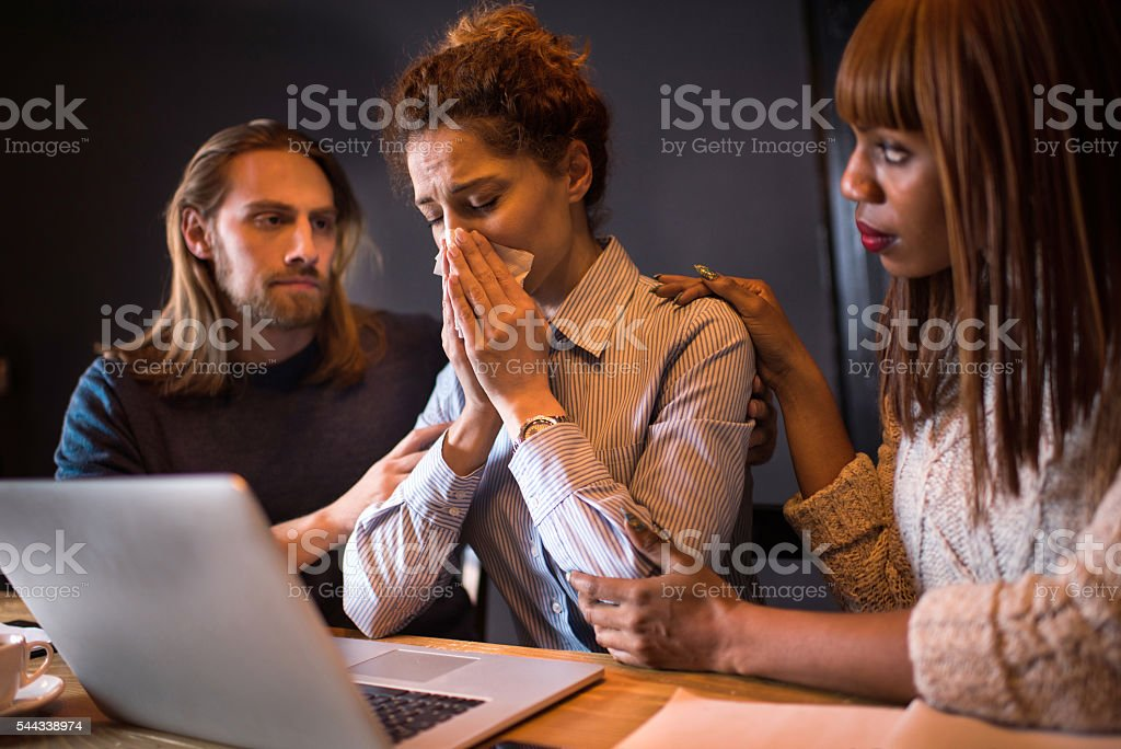 Sad businesswoman crying while her colleagues are consoling her. stock photo