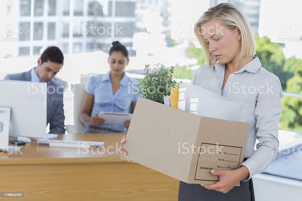 Sad businesswoman leaving office after being let go royalty-free stock photo