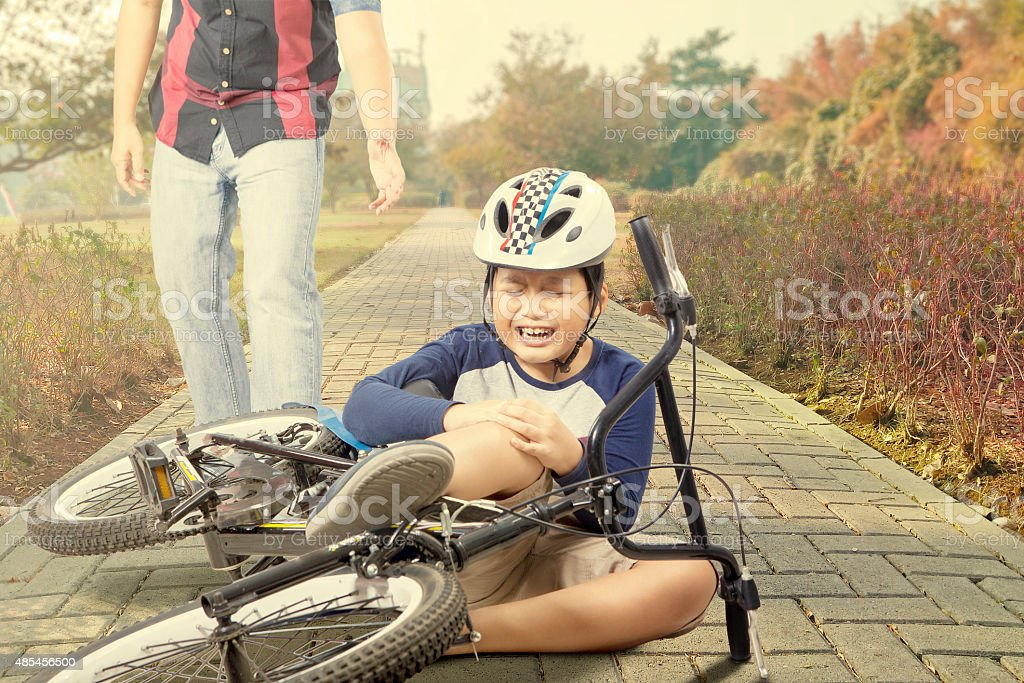 Sad child gets accident with his bike stock photo