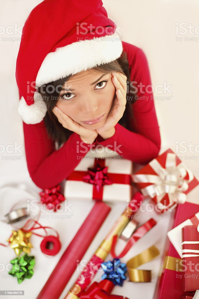 Sad christmas santa woman wrapping gifts royalty-free stock photo