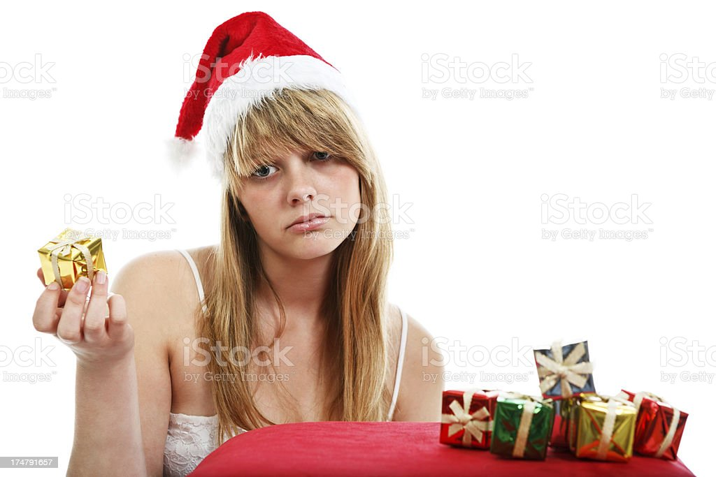 Sad Christmas teenage girl is disappointed by her gifts stock photo