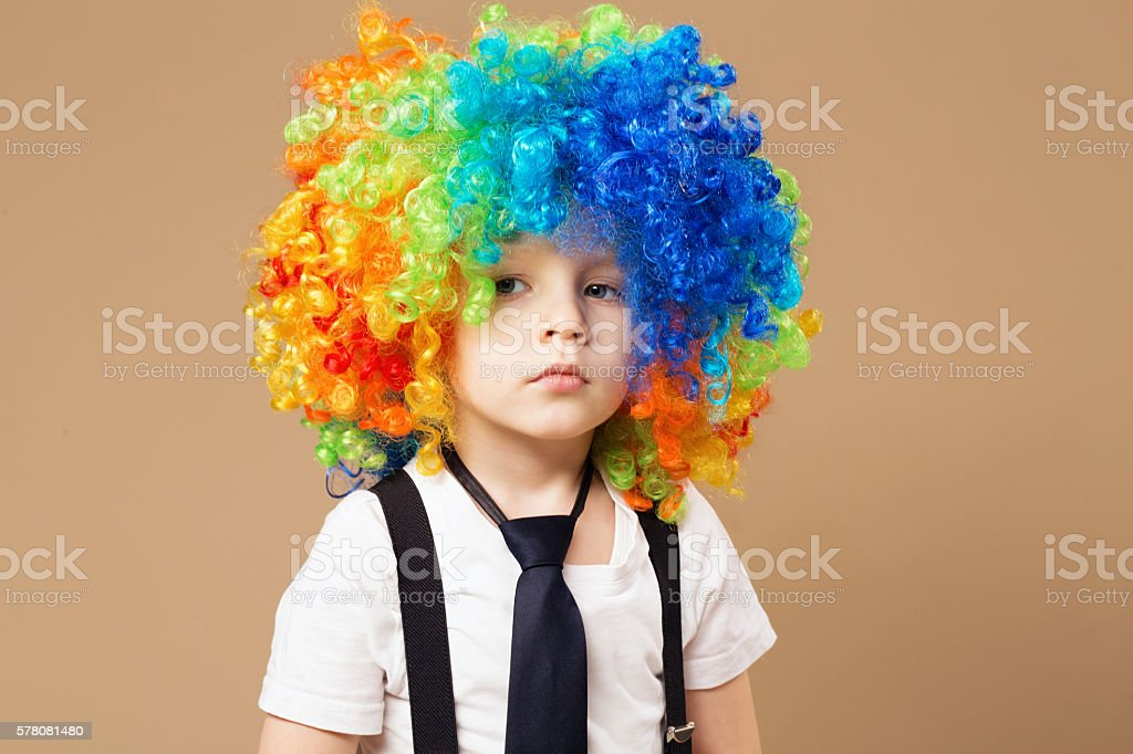 Sad clown boy with large colorful wig. stock photo
