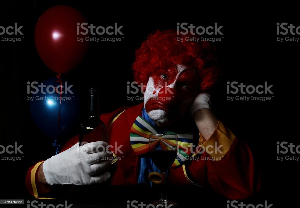 sad clown with balloons in background
