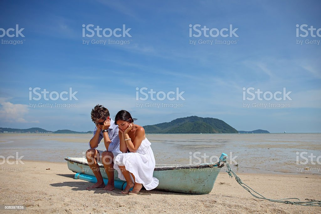 Sad couple on beach stock photo