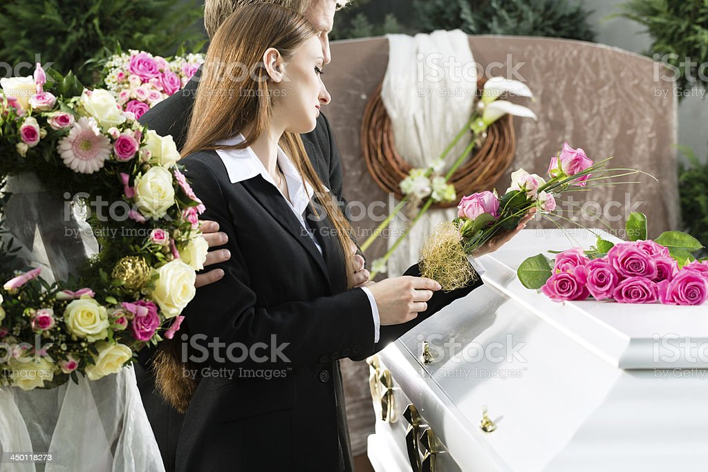 Sad couple placing flowers on a white casket at a funeral stock photo