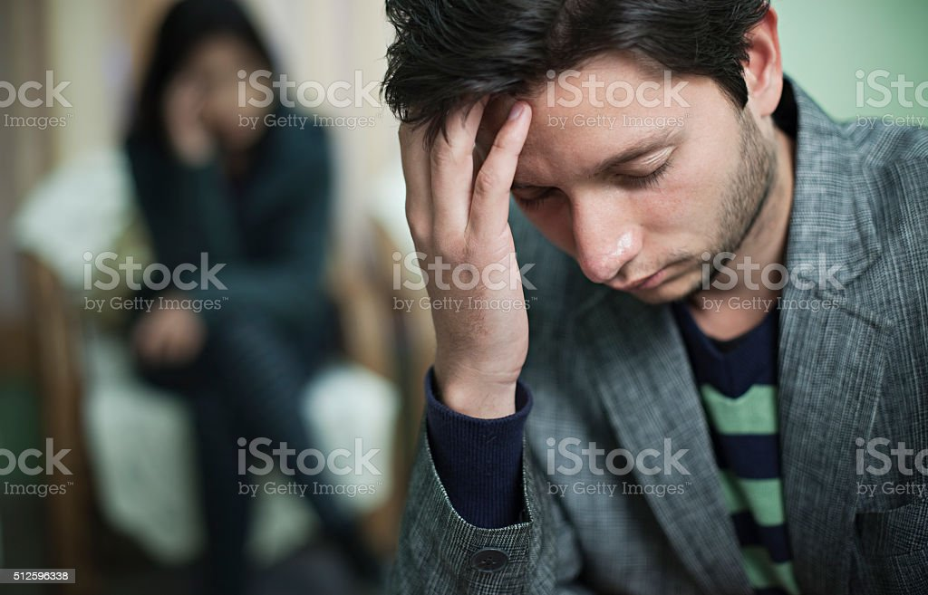 Sad couple, selective focus is on young man holding had. stock photo