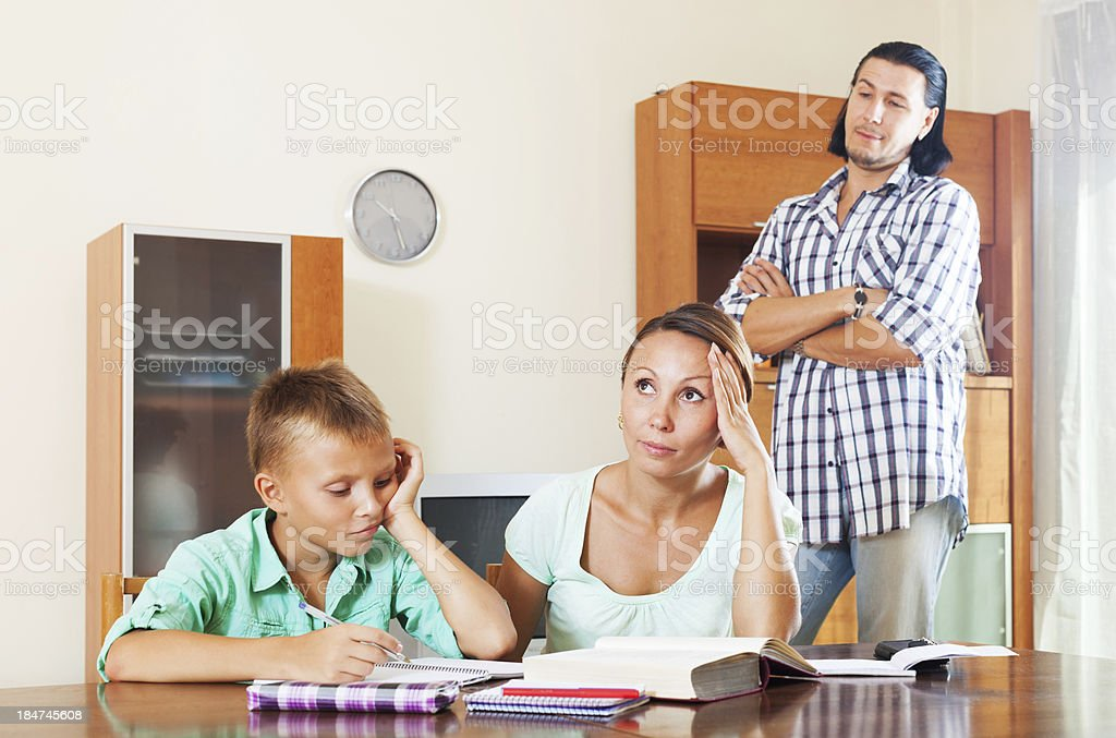 Sad couple with underachiever teenage boy doing homework royalty-free stock photo
